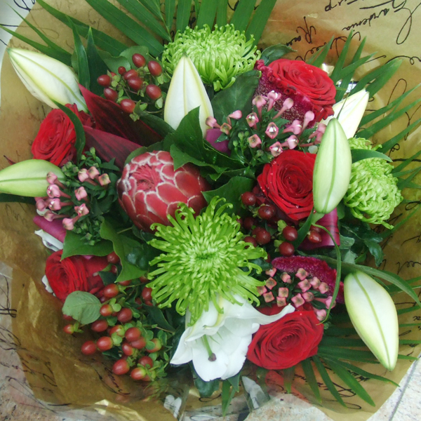 Flower arrangement of lilies, red roses and protea flowers