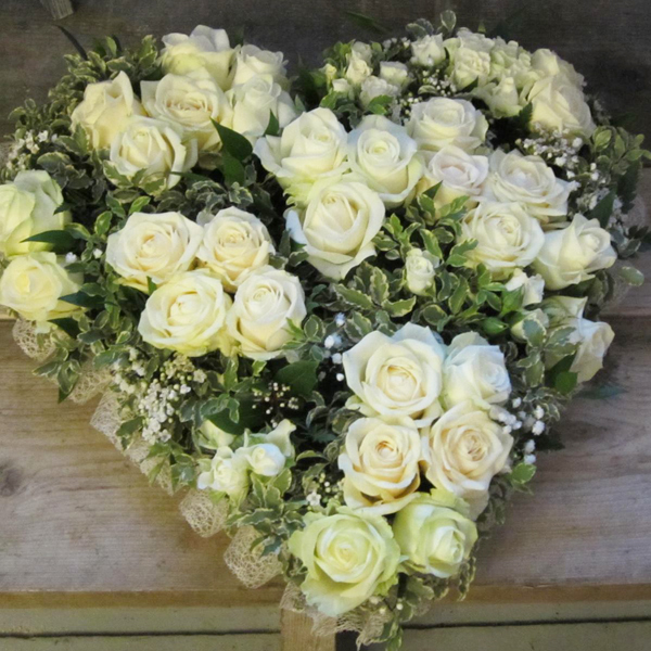 Heart floral arrangement of white roses and gyp with foliage