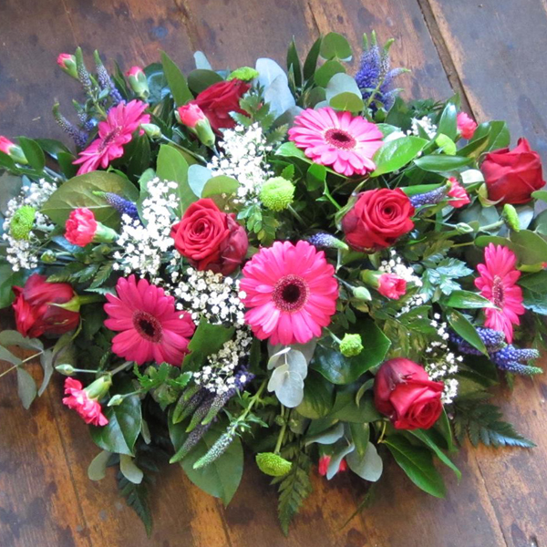 Open spray funeral tribute of red roses, pink gerberas and touches of purple flowers